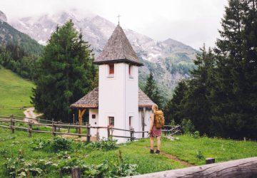 Pilgerwege in Deutschland - Wanderin mit Rucksack vor einer kleinen Kapelle auf einem Wanderweg.