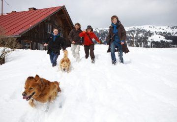 Winter Holiday: Activities - A family with dog in front of a hut in the snowy mountains.