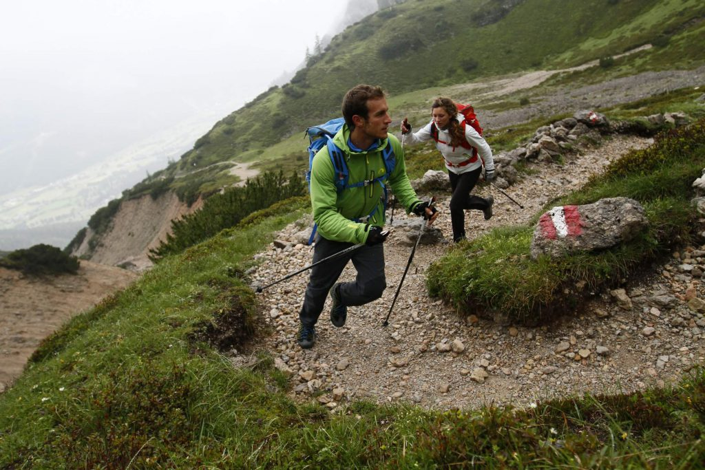 Speed Hiking Rothaarsteig Trail - A man and a woman with a backpack and trekking poles run uphill.