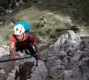 Touren Österreich und Schweiz - Kletterer mit Rucksack und Helm beim Besteigen eines Klettersteigs.