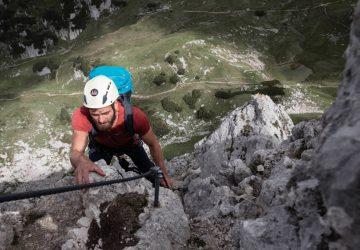 Climber with rucksack and helmet climbing a via ferrata.