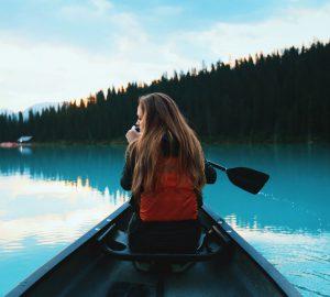 Basiswissen Paddeln im Kanadier - Frau in einem Boot auf einem See.