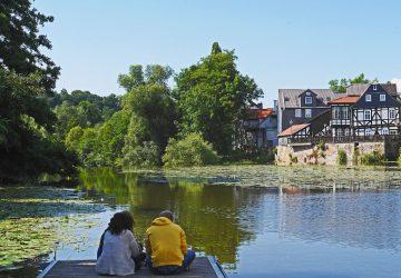 Paddeln auf der Lahn - Ein Paar sitzt auf einem Holzsteg am Fluss.