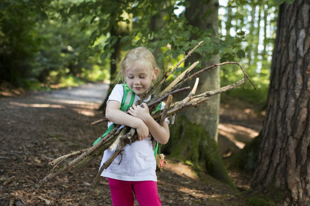 Girl with blond hair collects pieces of wood while hiking in the Allgäu.