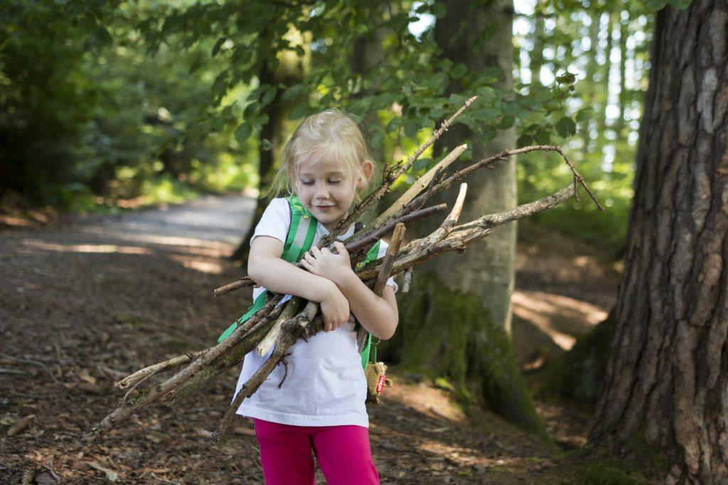 Mädchen mit blonden Haaren sammelt Holzstücke beim Wandern im Allgäu.