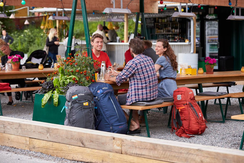 A group of backpackers with their backpacks in a cafe.