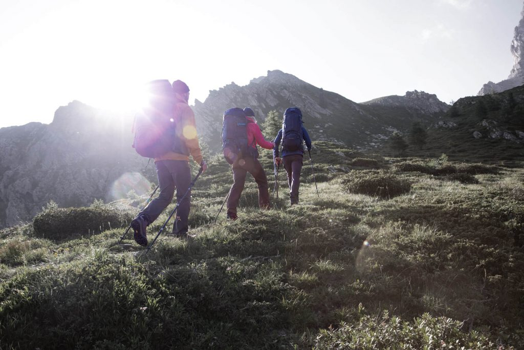 Drei Trekker laufen im Sonnenschein bergauf.