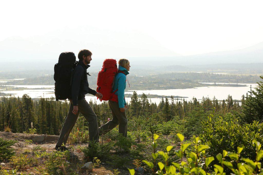 Zwei Trekker mit Rucksack in bewaldetem Gebiet.