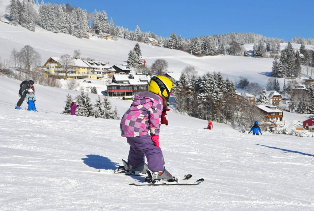 Skiing German Uplands - Little girl with a yellow helmet and pink-purple jacket skiing on a practice course in the Black Forest.