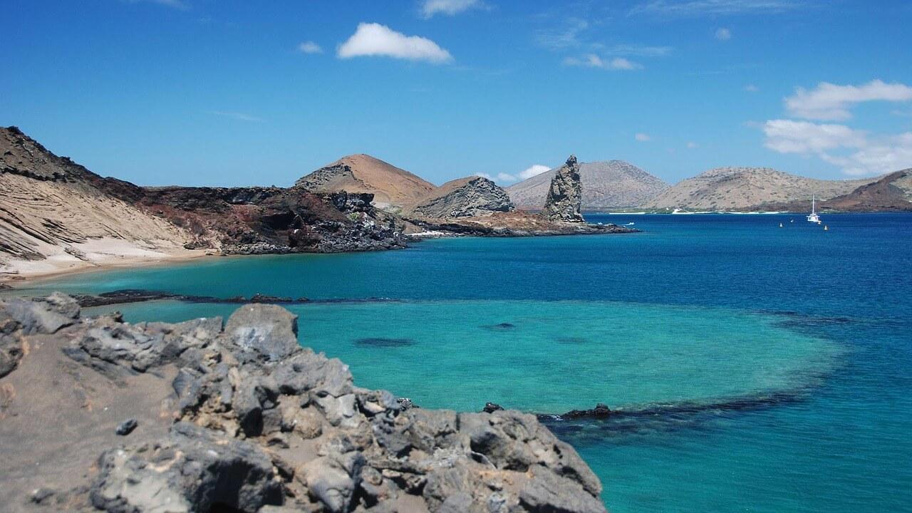 Reise nach Galapagos - türkisblaues Meer und felsige Küste.