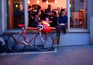 Copenhagen by bike - Girl sitting in front of a cafe.