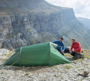 Wild camping tips - Two men pitching tents in the mountains.