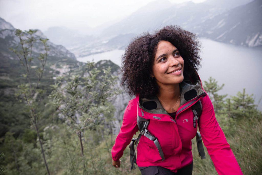 Frau beim Wandern mit Rucksack und Outdoor-Jacke.