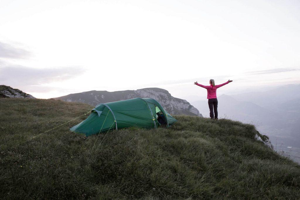 Frau neben einem Zelt in den Bergen mit ausgebreiteten Armen.