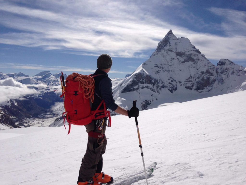 Ski touring enthusiasts look out over a distant mountain.