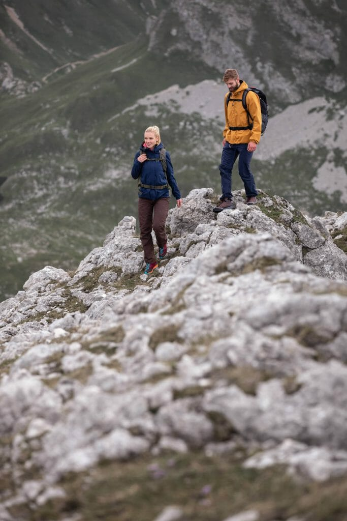 A woman and a man hiking in the mountains.