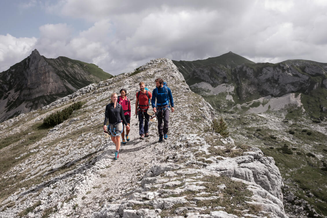 Eine Gruppe auf dem Weg zu einem Klettersteig in den Bergen.