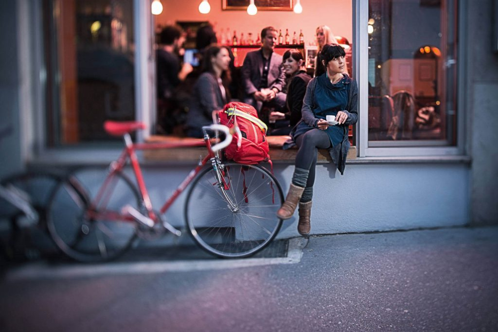Girl next to her bike in front of a bar with an espresso cup in her hand.