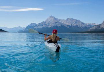 Paddeln leicht gemacht - Frau beim Kanu fahren auf einem See mit Berg im Hintergrund.