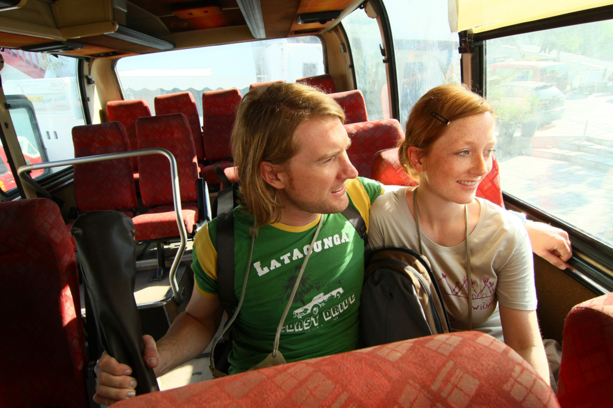 Backpacking insights - tips for a coach trip. A young couple is sitting on a bus.
