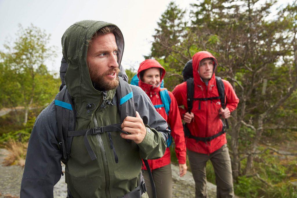 Drei Wanderer mit Regenjacken beim Wandern im Regen.