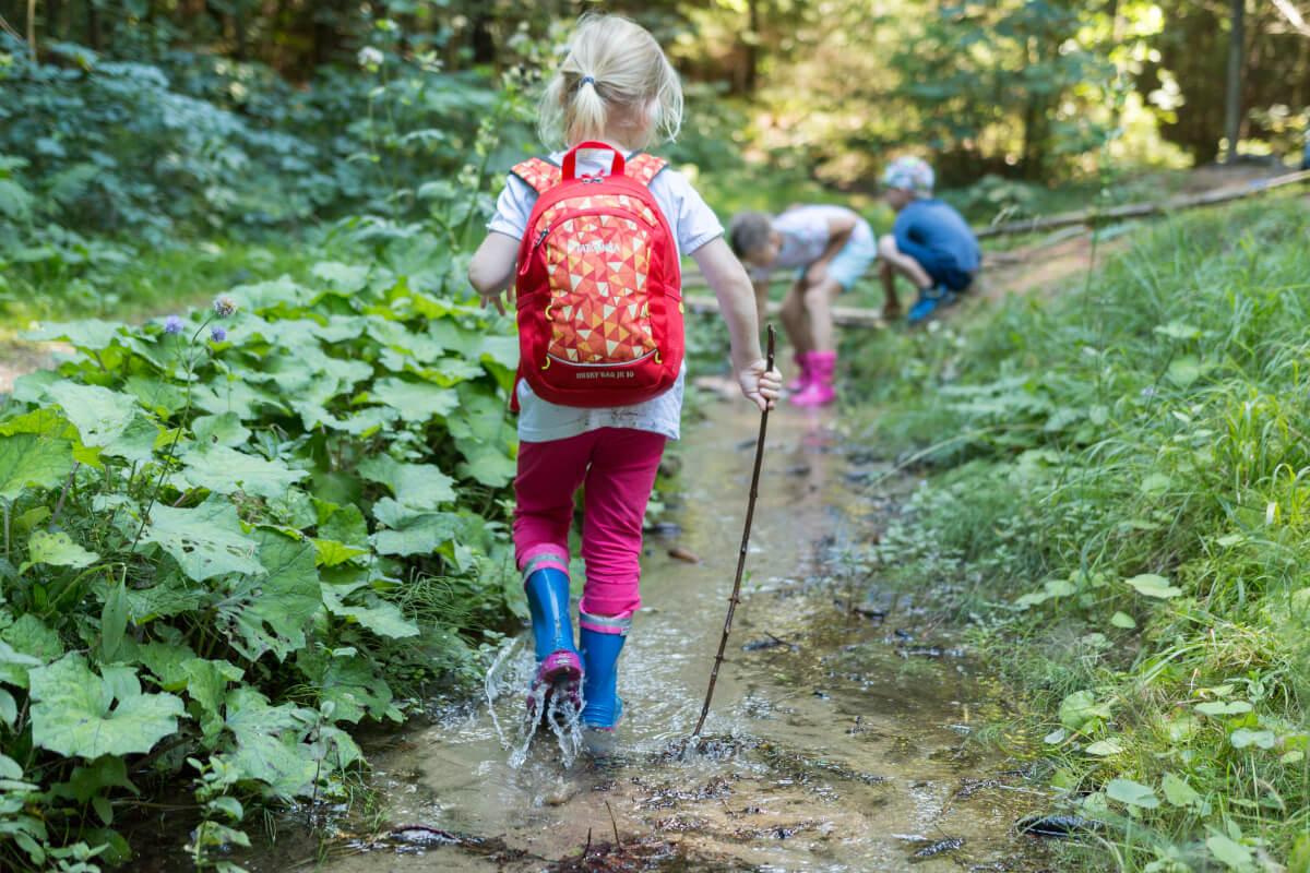 Wandern mit Kindern - Kleines Mädchen läuft mit ihrem Rucksack in einem Flussbett.