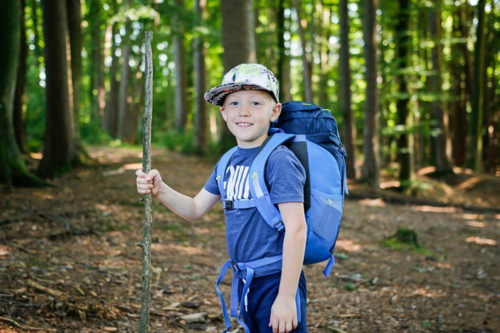 Wandern mit Kinder - Kleiner Junge mit Rucksack beim Wandern im Wald.