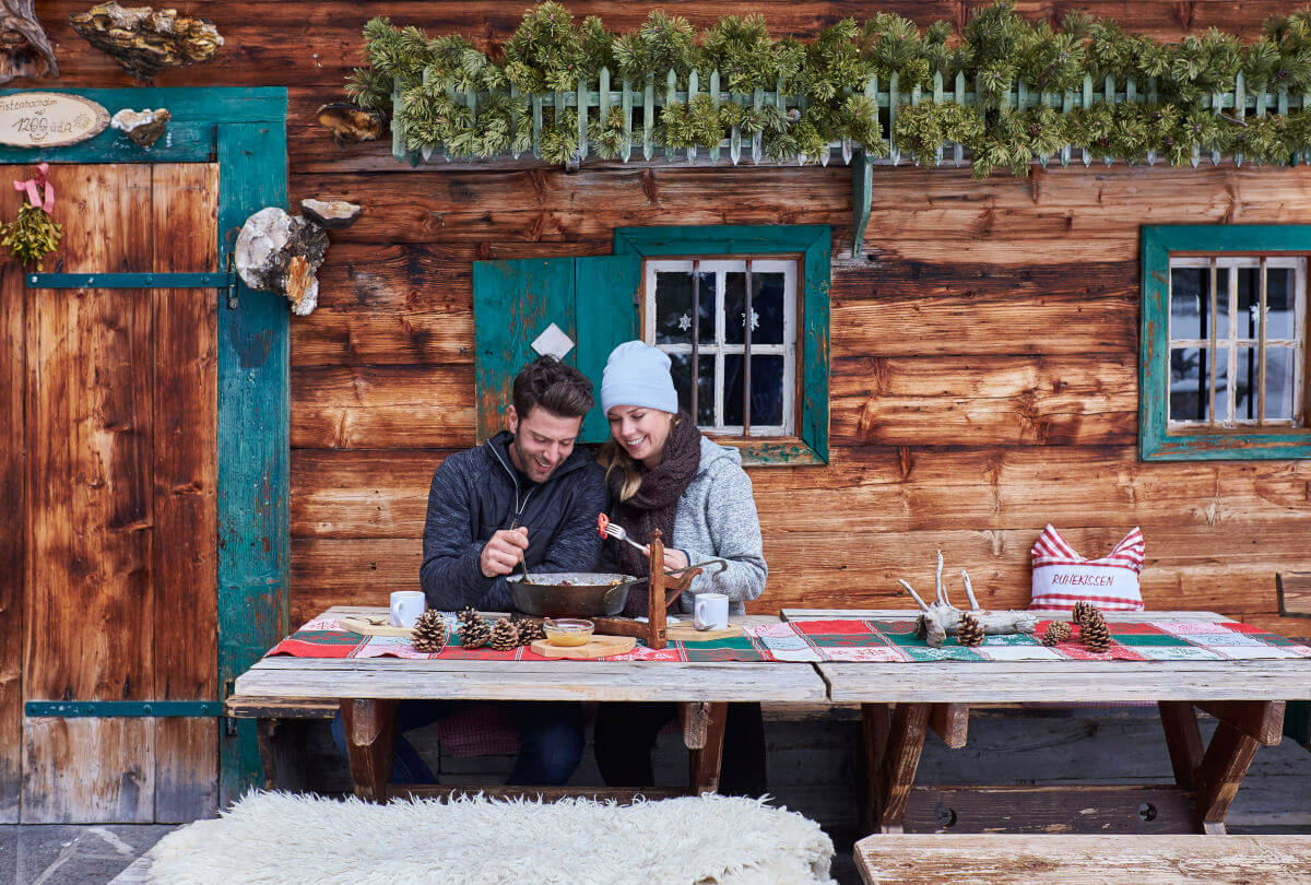 Winterurlaub - Junges Pärchen bei Brotzeit auf einer Hütte im Winter.