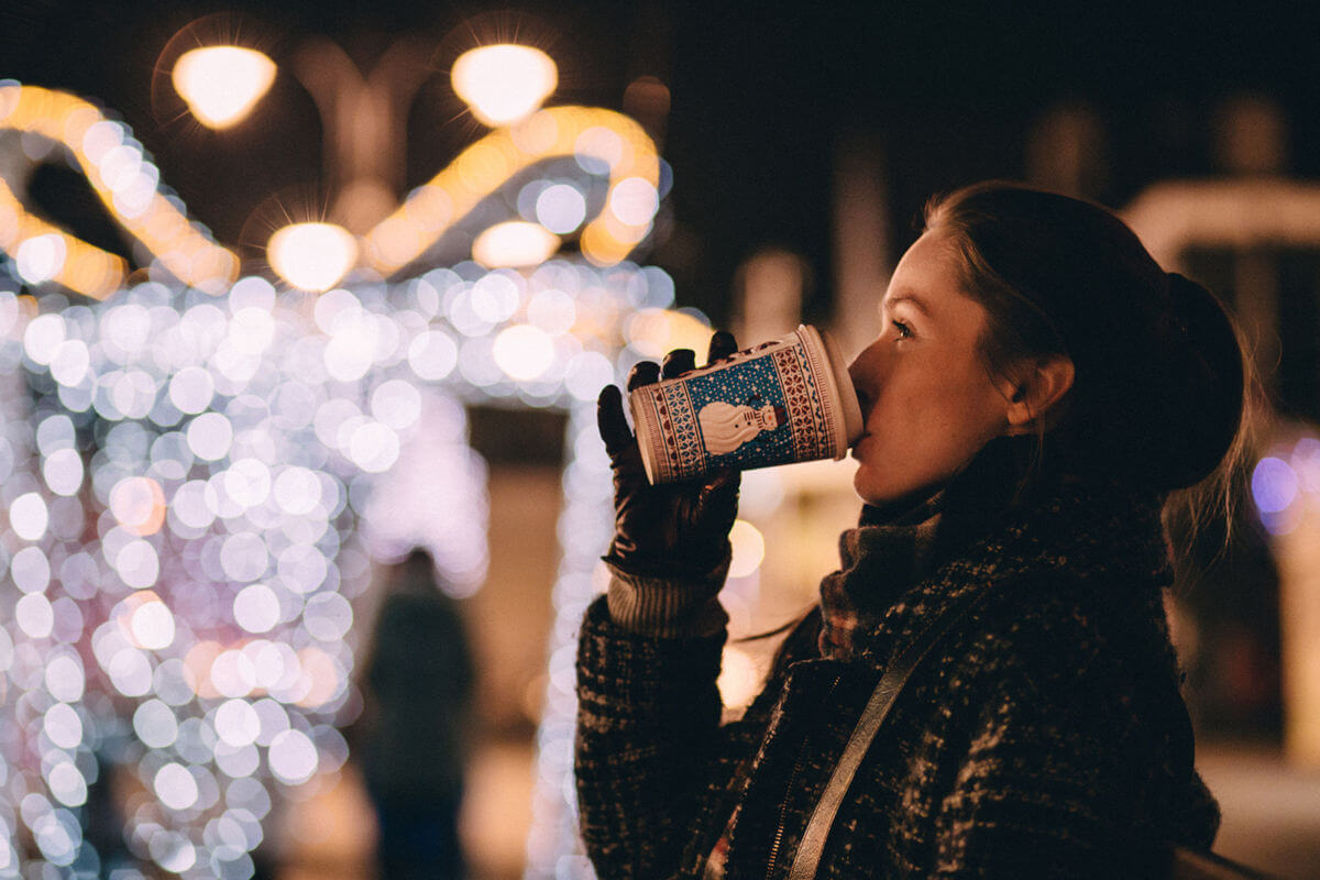 Städtereise nach London - Frau trinkt auf einem Weihnachtsmarkt aus einem Pappbecher. Foto: pexels, pixabay.