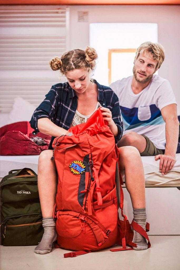 Richtig packen - Junge Backpackering beim Packen ihres Rucksacks.