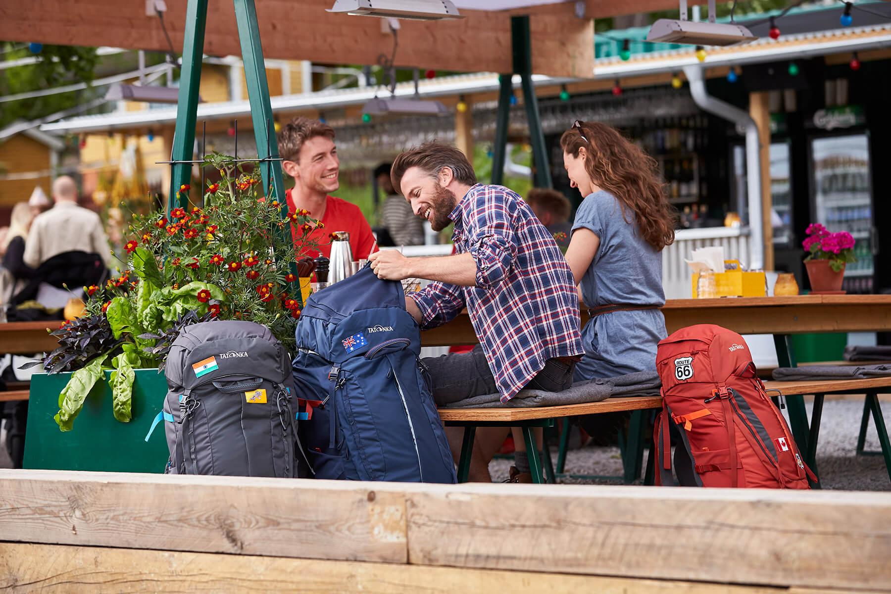 Eine Gruppe Backpacker mit ihren Rucksäcken in einer Bar.