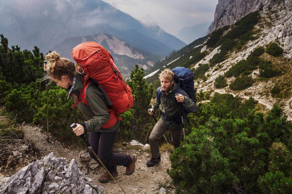 Frau und Mann mit großen Rucksäcken auf Trekking-Tour.