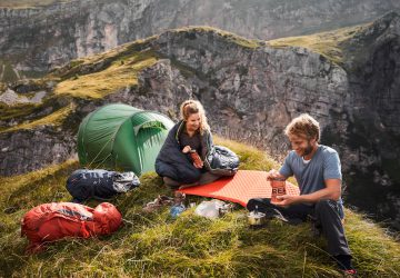 Ausrüstung Trekkingtour - Mann und Frau neben einem Zelt in den Bergen bei Kochen.
