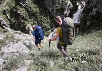 Bergwissen kompakt - Zwei Trekker mit großen Rucksäcken beim bergab laufen.