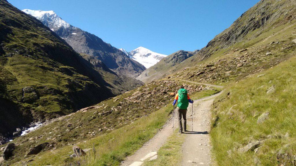 Wanderer mit grünem Rucksack auf dem Weg zur Similaun-Hütte im Ötztal. Im Hintergrund: der Similaun (3.606 m).