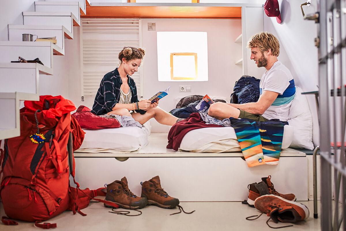 Flashpacker oder Backpacker - Ein Mann und eine Frau sitzen auf einem Bett in einem Hostel. Vor ihnen: Schuhe und ein roter Rucksack.