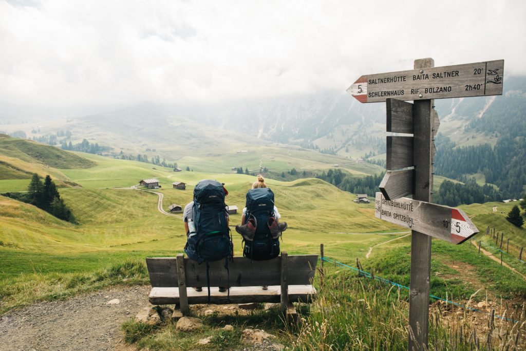 Hiking in South Tyrol - Two hikers take a break on a bench.