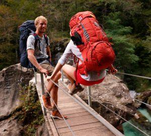 Zwei Backpacker auf einer Hängebrücke im Soca Tal in Slowenien.