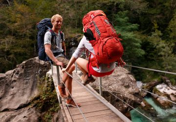Two backpackers on a suspension bridge in the Soca Valley in Slovenia.