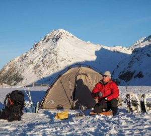 Michael Bösiger vor seinem Tatonka-Zelt beim Wintercamping in den schweizer Bergen.