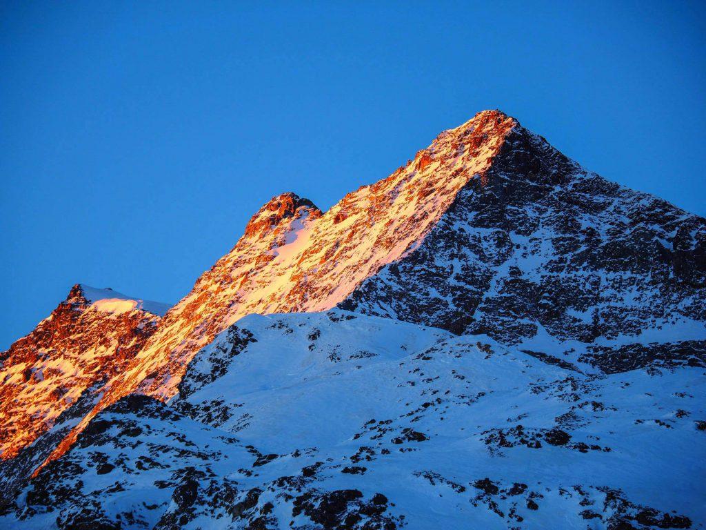 Sonne scheint auf einen schneebedeckten Berg in der Schweiz.