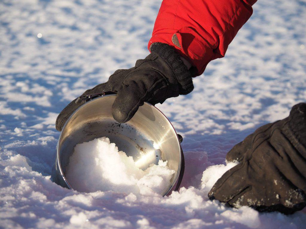 Tatonka Mitarbeiter Michael Bösiger befüllt eine Schüssel mit Schnee.