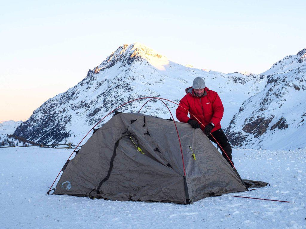 Tatonka Mitarbeiter Michael Bösiger beim Aufbau seines Zeltes beim Wintercamping in den schweizer Bergen.