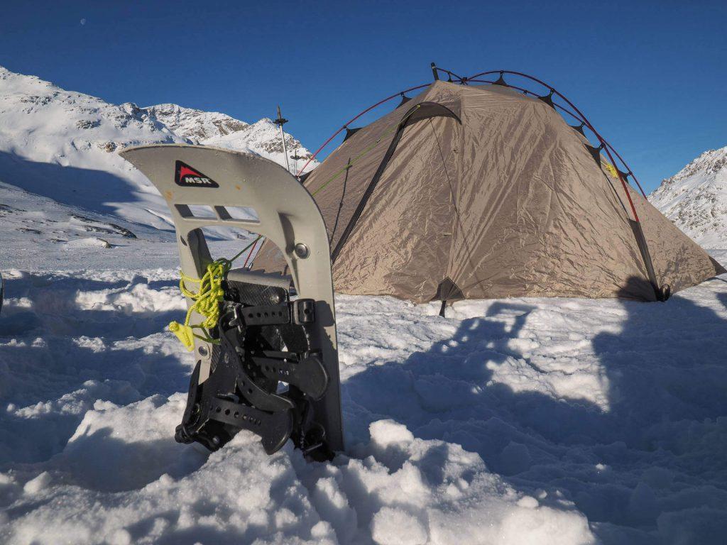 Schneeschuh als Hilfsmittel beim Abspannen eine Zeltes beim Wintercamping.