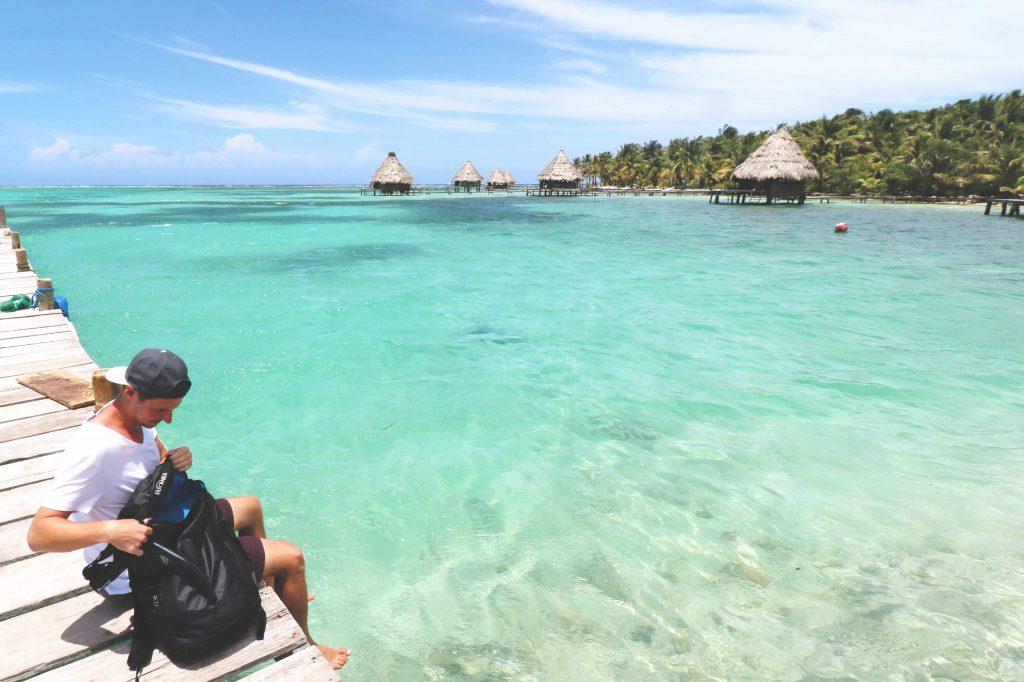 Daniel sitzt auf einem Steg der Insel Laughing Bird Caye vor der Küste von Belize und blickt auf das glasklare Wasser.