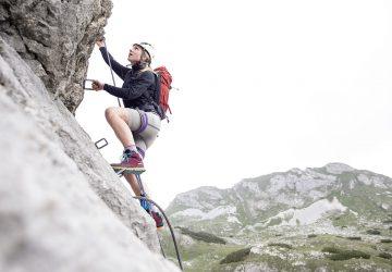 Klettersteige - Frau mit rotem Rucksack und weißem Helm beim Besteigen eines Klettersteiges.