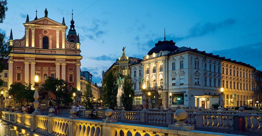 Die Altstadt von Ljubljana in der Abenddämmerung mit Brücke und beleuchteten Gebäuden.