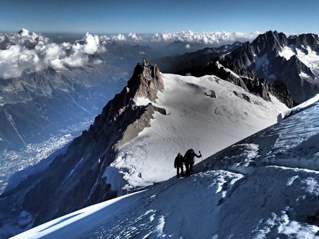 Blick zurück auf zwei Bergsteiger. Im Tal sind die Häuser zu erkennen.