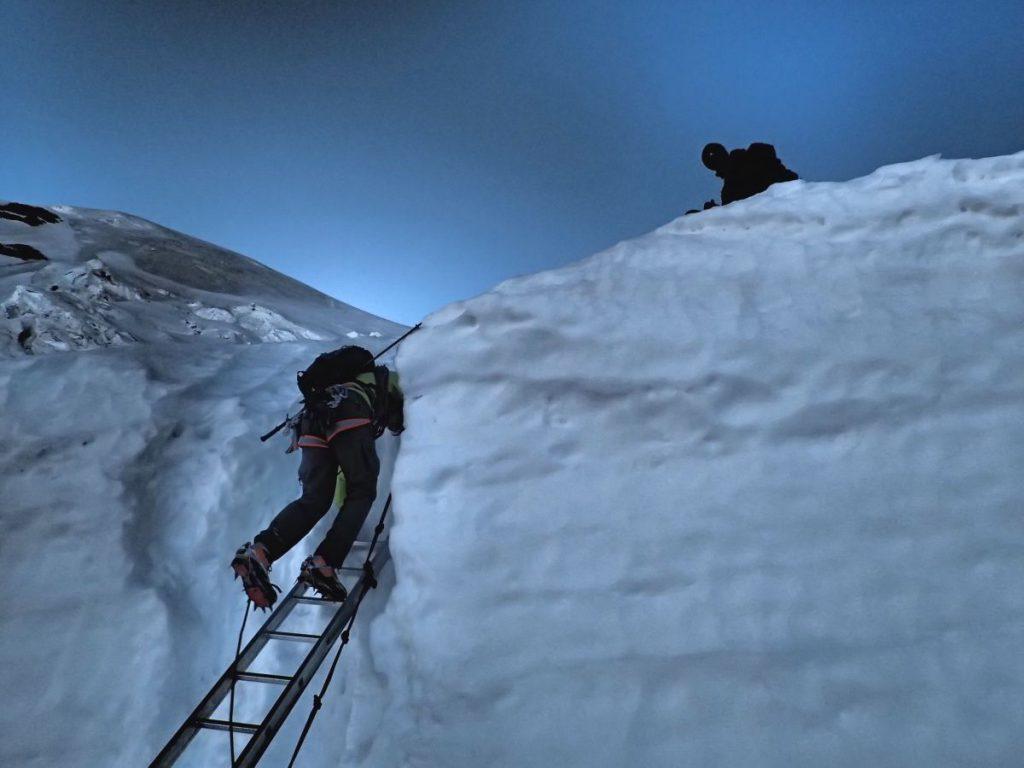 Einer der Bergsteiger überwindet auf einer Leiter eine Gletscherspalte.