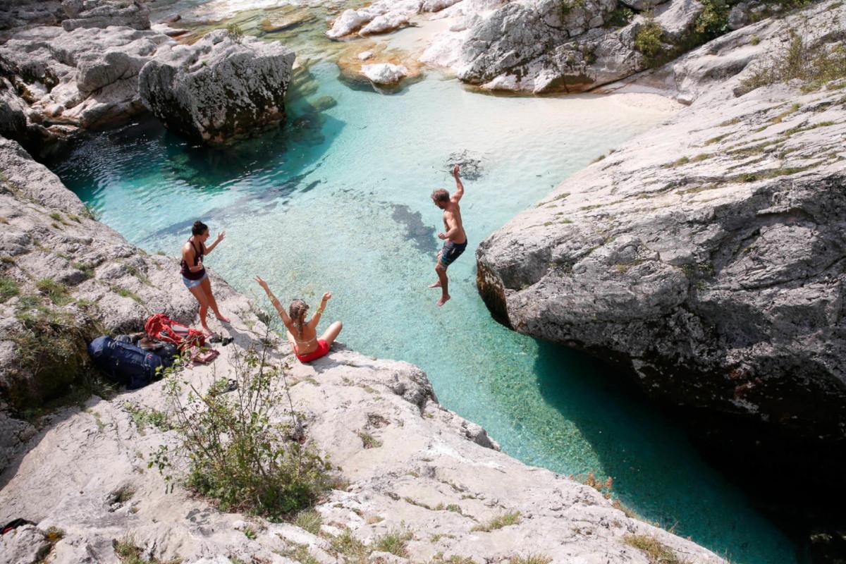 Outdoor-Hygiene - Eine Gruppe von Trekkern springt in einen Bergsee.